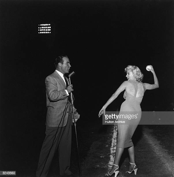 American actor Marilyn Monroe prepares to throw a baseball wearing high heels and a dress as American emcee Ralph Edwards speaks into a microphone on...