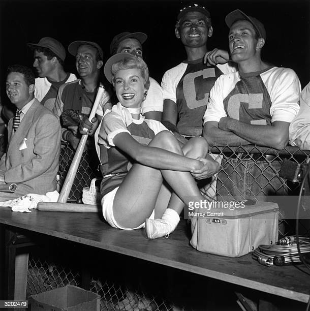 EXCLUSIVE American actor Janet Leigh sits on a dugout bench while her teammates actor Vince Edwards jazz trumpeter Harry James and actors Tony Dante...
