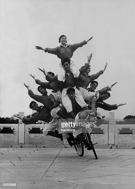 Ten Chinese acrobats balancing on a bicycle in Paris