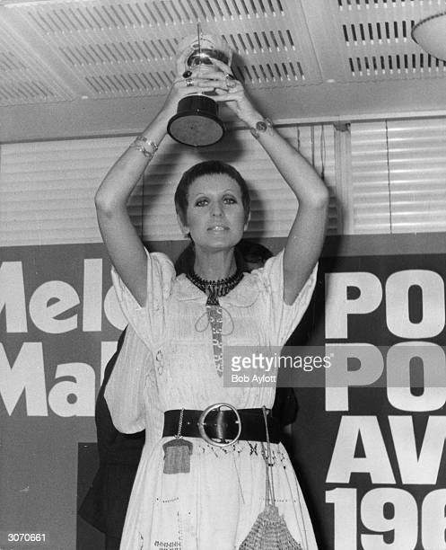 Britain's top female singer Julie Driscoll holds her trophy aloft after the Melody Maker Pop Poll Awards