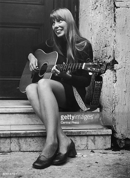 Canadian folk singer and songwriter Joni Mitchell strumming her guitar outside The Revolution club in London