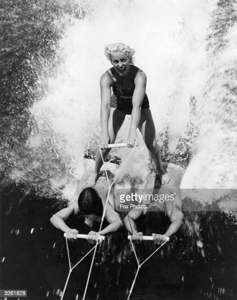 Barbara Clack skis on human waterskis Joker Osborn and Ken White champion skiers at Cypress Gardens Florida