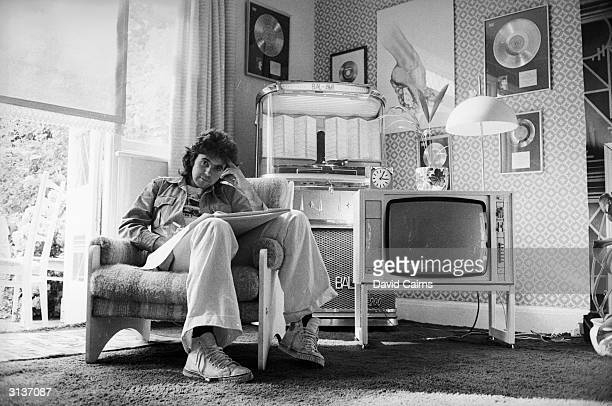 English pop singer and teen idol David Essex relaxes at home surrounded by some of his awards