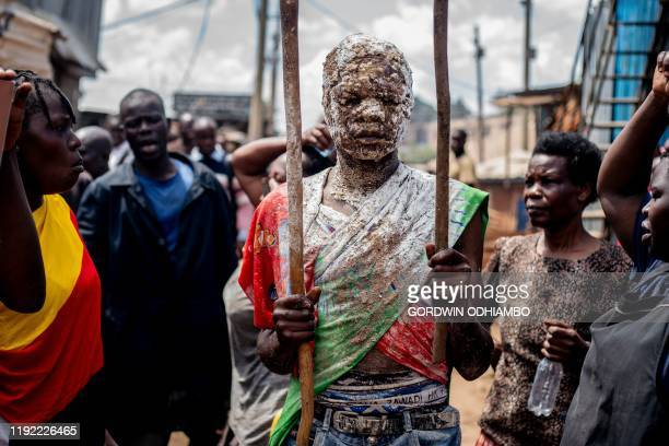 TOPSHOT 18yearold Isaac Namolo from Gisu tribe is smeared by local brew around his head for his circumsicion at Kibera slum in Nairobi Kenya on...