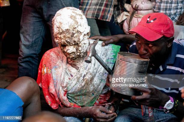 Year-old Isaac Namolo from Gisu tribe is smeared by local brew around his head as he drinks local brew for his circumsicion at Kibera slum in...