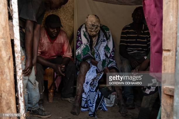 Year-old Isaac Namolo from Gisu tribe, sits with local brew around his head as he is consoled by elders after being circumcised at Kibera slum in...