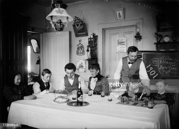 1900s 1901 TURN OF 20 CENTURY FAMILY THREE GENERATIONS AT KITCHEN TABLE NEW YEARS CELEBRATION