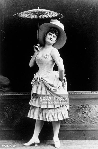 1900s 1910s ANONYMOUS UNIDENTIFIED WOMAN THEATER ACTOR POSED IN FASHIONABLE RUFFLED SKIRT DRESS HAT PARASOL LOOKING AT CAMERA