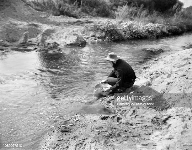 1900s MAN PROSPECTOR PANNING FOR GOLD IN STREAM