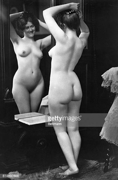 Nude young woman in front of a mirror during toilette
