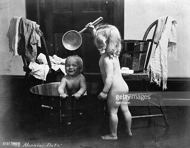 1905The morning bath Girl uses tin pan to provide shower for her baby brother 1905 BPA2# 436 Not available for use as framed art reproduction for...