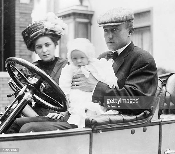 Mr. & Mrs. Ty Cobb and baby in Owen car. Ty is holding the child.
