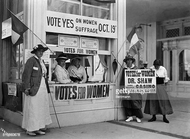 Women stand at a women's suffrage information booth encouraging people to vote yes for women's voting rights Some women are also standing beside the...