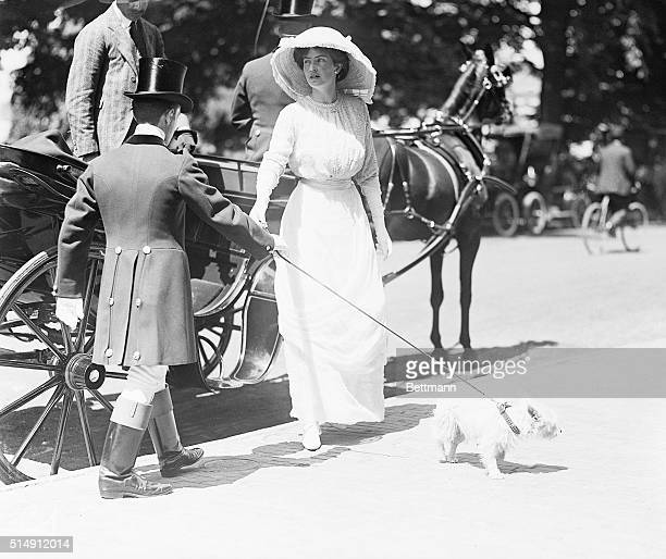 Photo shows Mrs Robert Goelet Jr having stepped from a carriage about to take the leash of her small dog from the driver