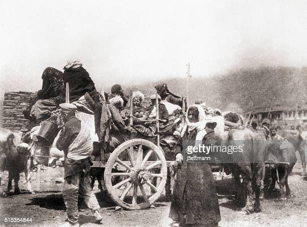 Photo shows Armenian refugees fleeing the Turks. They have a number of wagons loaded with supplies.