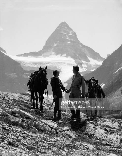 1920s 1930s COUPLE MAN WOMAN SILHOUETTED HOLDING HANDS STANDING WITH HORSES IN MOUNTAINS WESTERN MT ASSINIBOINE CANADA