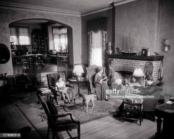 1920s 1930s Family Woman Mother Boy Son Girl Daughter Pet Dog Sitting Together In Upscale Living Room Reading Around Fireplace