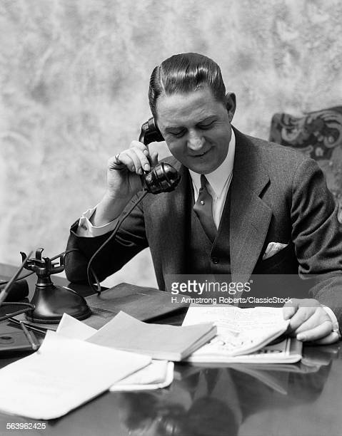 1920s 1930s MAN SITTING AT...