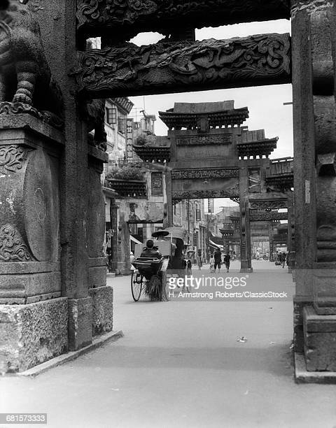 1920s 1930s RICKSHAW ON STREET IN CANTON CHINA UNDER ORNATE CARVED ARCHES ANCIENT PAI-LOUS CHINESE ARCHITECTURE