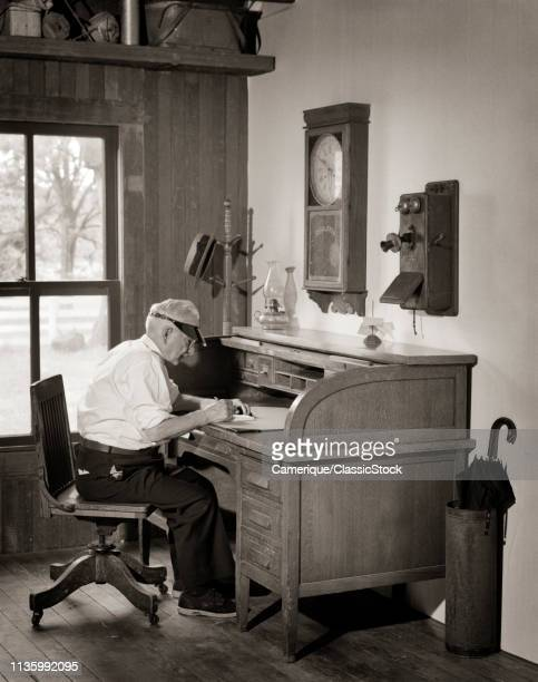 1920s 1930s SENIOR MAN WEARING VISOR SITTING IN OFFICE AT ANTIQUE WOODEN ROLLTOP DESK WITH WOODEN CRANK TELEPHONE ON WALL