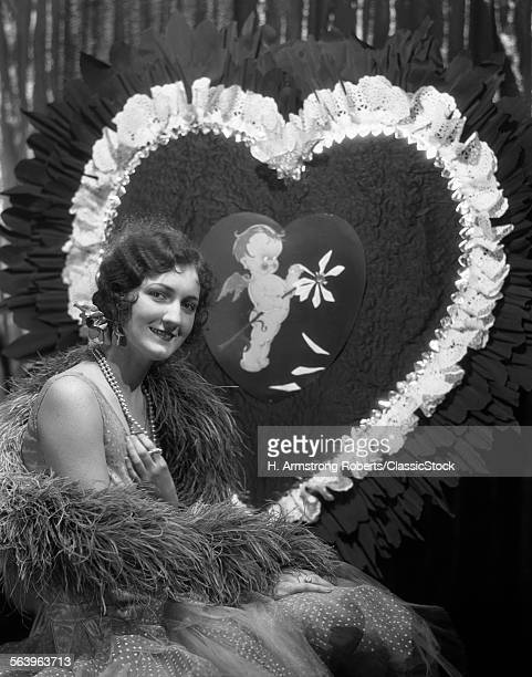 1920s 1930s SMILING YOUNG WOMAN LOOKING AT CAMERA FINGER WAVE HAIR PEARLS FEATHER BOA GIANT VALENTINE HEART