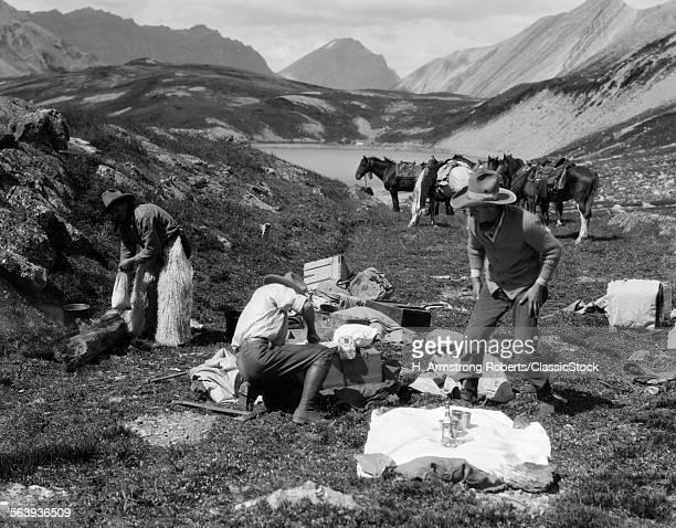 1920s 1930s THREE MEN COWBOYS AT CAMPSITE PREPARING FOOD HORSES IN BACKGROUND ALBERTA CANADA
