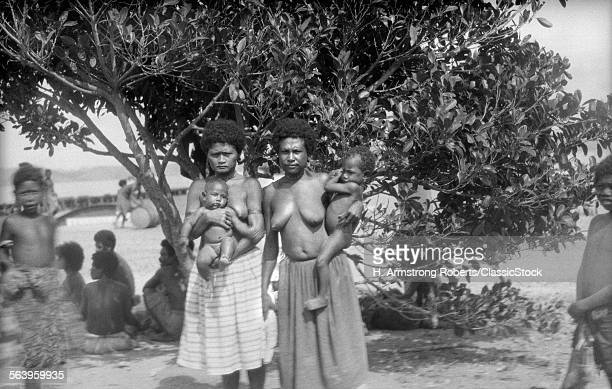 1920s 1930s TWO NATIVE WOMEN MOTHERS TOPLESS WEARING SKIRTS HOLDING INFANT BABY CHILDREN NEW GUINEA