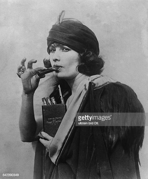 PROHIBITION 1920s A woman using a dummy book bearing the title 'The Four Swallows' as a hiding place for liquor during Prohibition 1920s