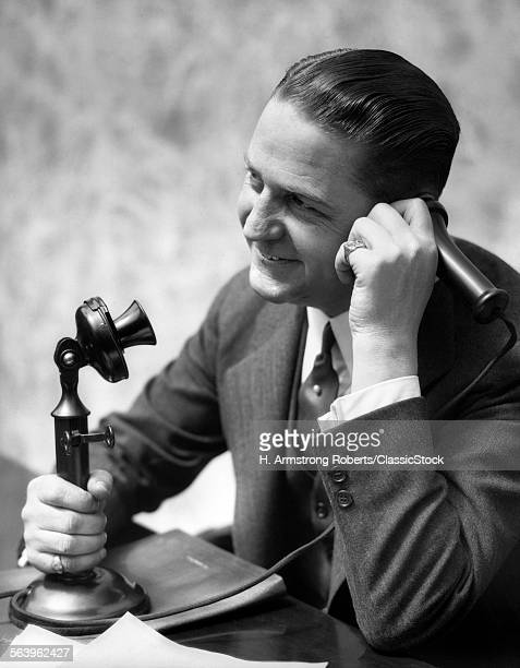 1920s BUSINESSMAN TALKING INTO CANDLESTICK TELEPHONE
