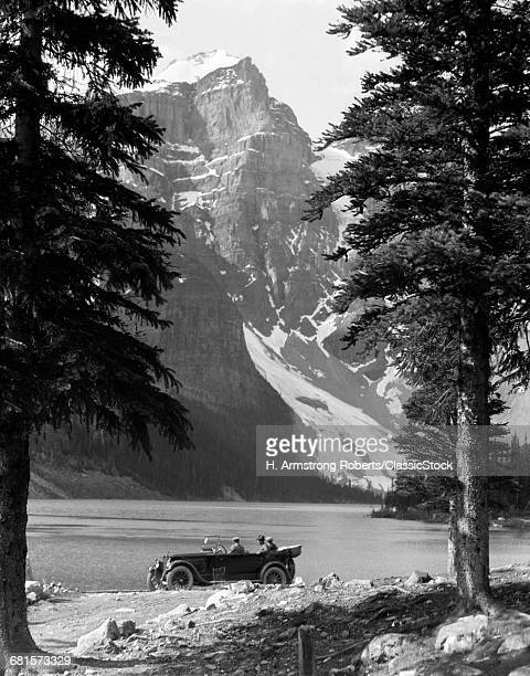 1920s COUPLE IN TOURING CAR OBSERVING MORAINE LAKE IN BANFF NATIONAL PARK ALBERTA CANADA