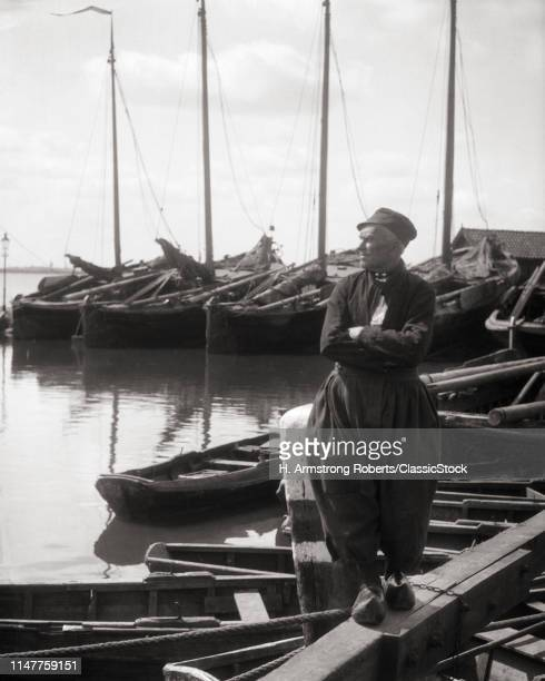 1920s DUTCH MAN WEARING TRADITIONAL CLOTHING CLOTH CAP LONG SLEEVE SHIRT VOLUMINOUS PANTS WOODEN SHOES VOLENDAM HARBOR HOLLAND