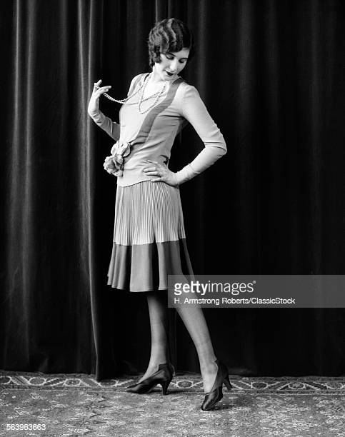 1920s FLAPPER WOMAN POSING HAND ON HIP HOLDING STRING OF PEARLS STRETCHING LEG CHECKING HOSIERY SEAMS
