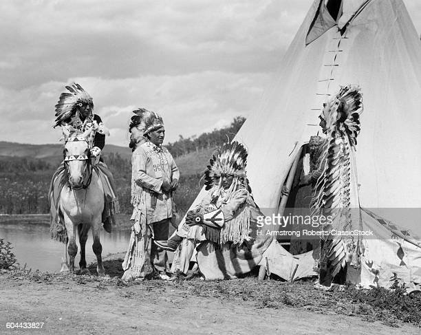 1920s FOUR NATIVE AMERICAN STONEY SIOUX INDIAN MEN ASSEMBLED BESIDE TEPEE WEARING FULL EAGLE FEATHER WAR BONNETS ALBERTA CANADA