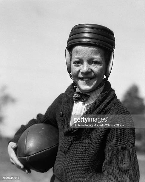 1920s FRECKLEFACED BOY IN SWEATER BOW TIE WEARING LEATHER FOOTBALL HELMET HOLDING FOOTBALL UNDER ARM LOOKING AT CAMERA