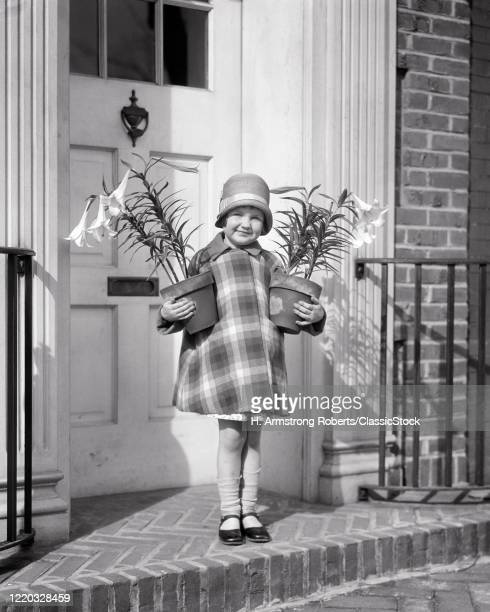 1920s girl wearing cloche hat plaid coat mary jane shoes socks falling down holding two pots of easter lilies at front door