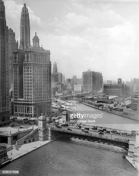 1920s high angle view looking west above the Chicago River with Michigan Ave bridge in the foreground Wacker Drive winds along the south bank of the...