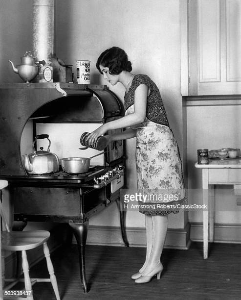 1920s HOUSEWIFE AT STOVE...