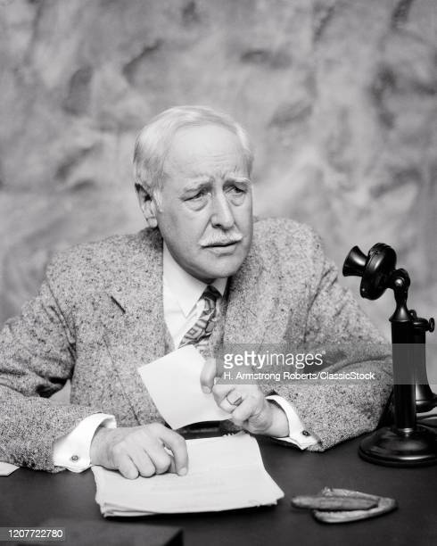 1920s mature businessman at desk clutching paper concerned facial expression cigar in ashtray candlestick phone on desk.