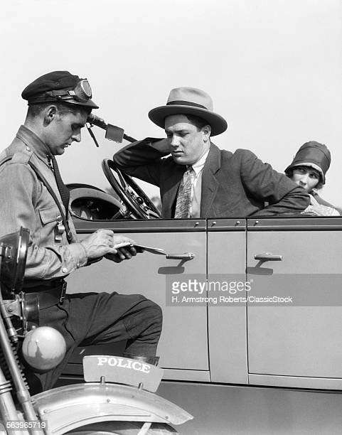 1920s MOTORCYCLE POLICEMAN WRITING A SPEEDING TICKET TO A COUPLE SITTING IN CONVERTIBLE SEDAN