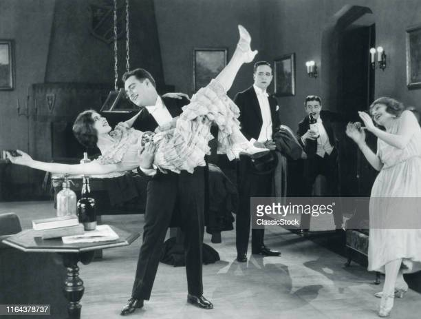 1920s Movie Still Of Wild Party With Woman Flapper Turned UpsideDown In Arms Of Man Dancing