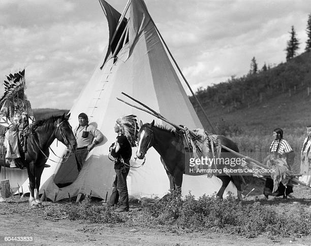 1920s NATIVE AMERICAN STONEY SIOUX INDIAN GROUP MEN AND WOMEN WITH HORSE PULLING TRAVOIS BY TEPEE ALBERTA CANADA
