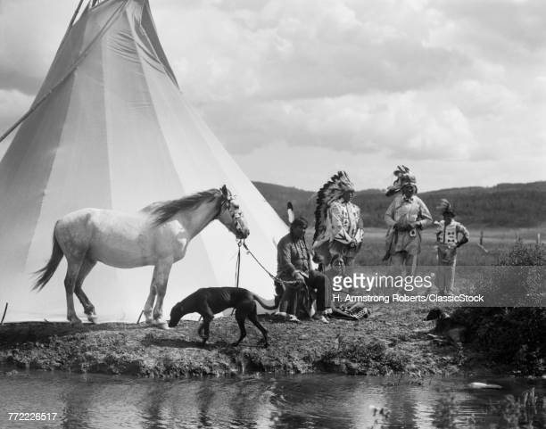 1920s NATIVE AMERICAN INDIAN GROUP BY TEPEE MAN WOMAN CHILD HORSE DOG STONEY SIOUX TRIBE NEAR ALBERTA CANADA