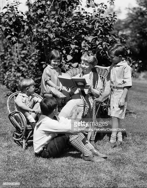 1920s OLDER WOMAN GRANDMOTHER SITTING IN WICKER CHAIR READING BOOK TO FOUR BOYS GIRLS GRANDCHILDREN