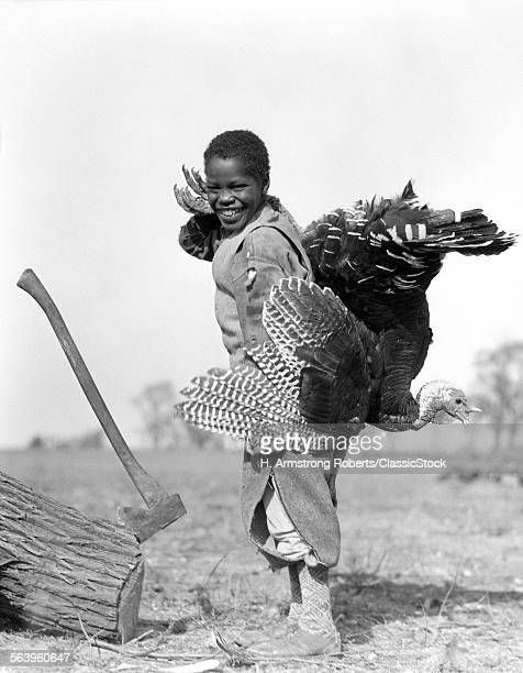 1920s SMILING ANONYMOUS AFRICAN AMERICAN BOY IN KNICKERS LOOKING AT CAMERA HOLDING A LIVE TURKEY STANDING BY A LOG WITH AN AX