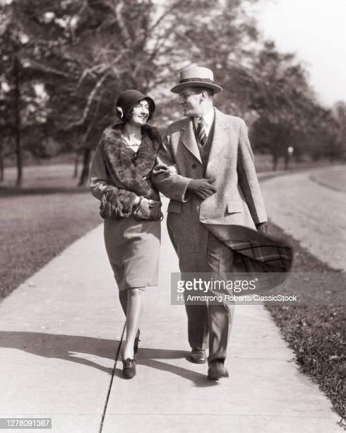1920s Smiling Couple Man Woman Husband Wife Walking Arm In Arm Down Street Wearing Coats And Hats Gloves Looking At Each Other
