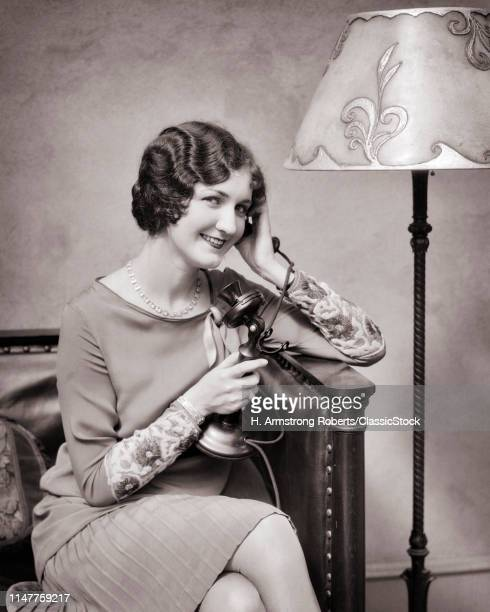 1920s SMILING WELL DRESSED WOMAN TALKING ON CANDLESTICK TELEPHONE