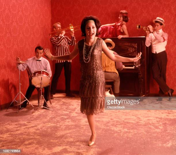 1920s SPEAKEASY SCENE WOMAN FLAPPER SILVER BEADED DRESS DOING THE CHARLESTON IN FRONT OF A BAND