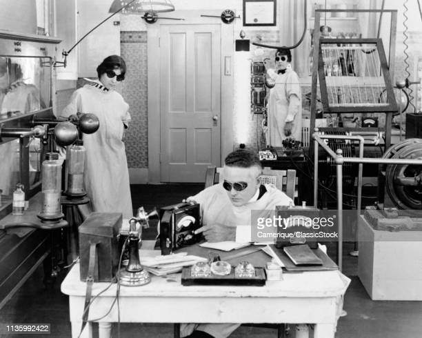 1920s THREE MAD SCIENTISTS WORKING EXPERIMENTING INVENTING IN ELECTRONICS LABORATORY ALL WEARING DARK GOGGLES WHITE LAB COATS