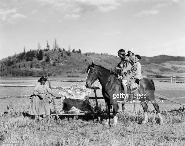 1920s THREE NATIVE AMERICAN CHILDREN ON HORSEBACK TALKING TO WOMAN TANNING HIDE STONEY SIOUX ALBERTA CANADA