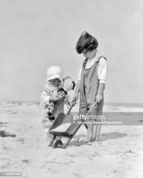 1920s TWO KIDS ON THE BEACH BOY WITH TOY WHEELBARROW FULL OF SAND AND BABY GIRL HOLDING RAGGEDY ANDY DOLL